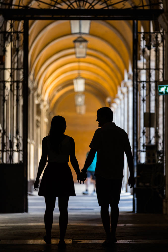 Couple in silhouette holding hands during photo shoot