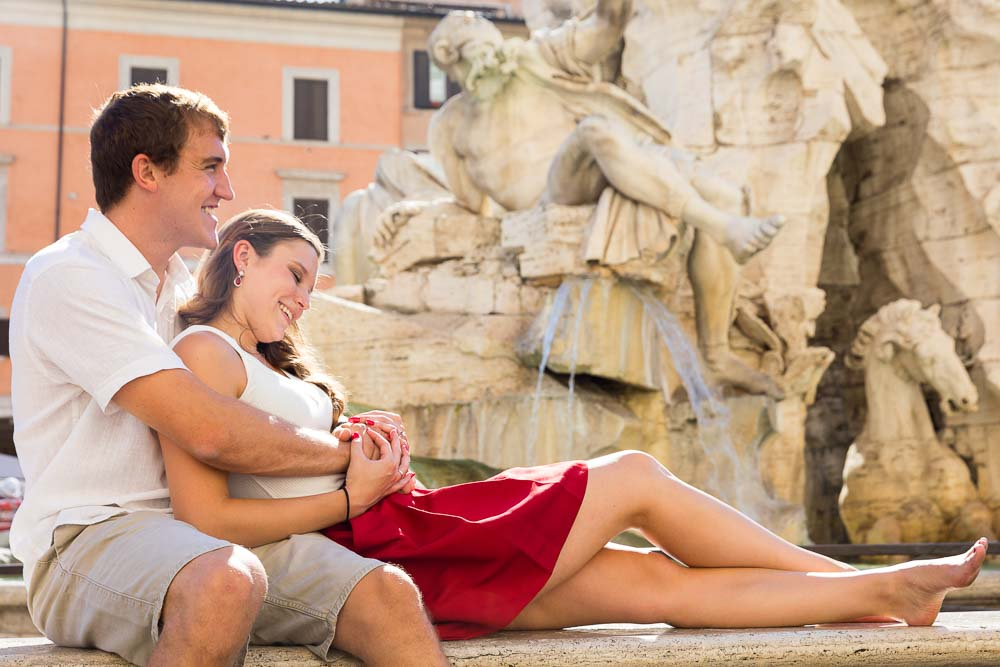 Portrait picture together on a marble bench under Piazza Navona's water fountain statues