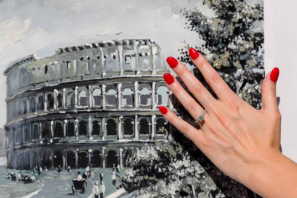 Photo of the engagement ring by a Colosseum painting. Engaged in Rome