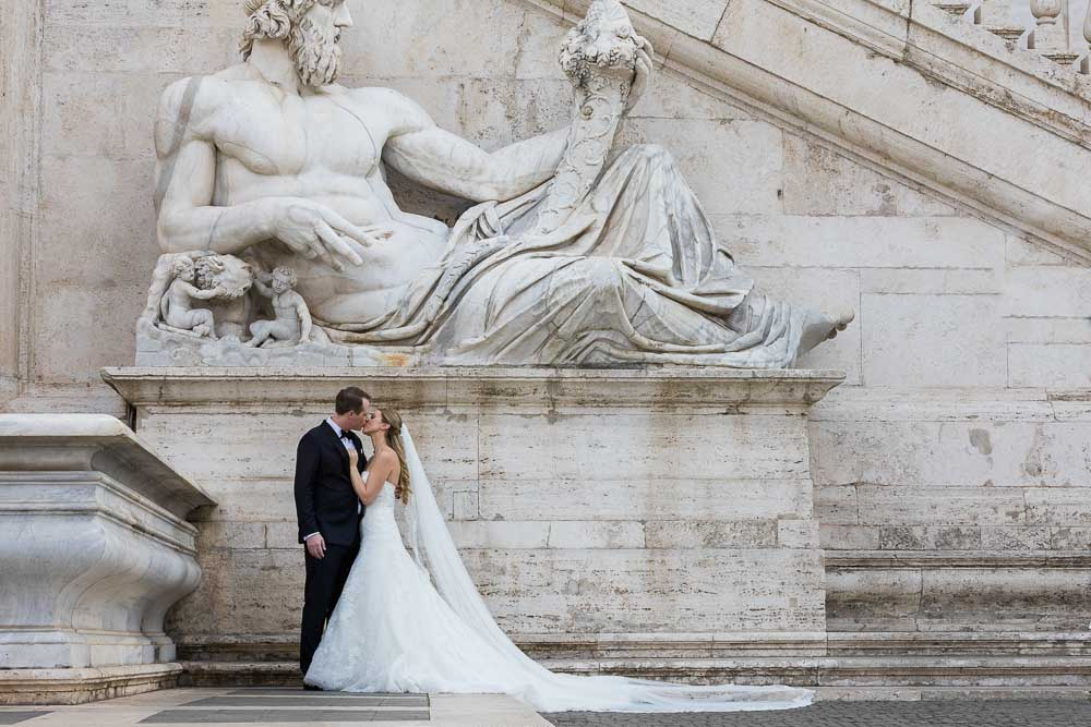 Married couple posing underneath an ancient roman statue in Piazza del Campidoglio in Rome