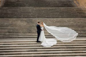 Wedding pictures with bride and groom on the a scenic roman staircase with the veil up in the air