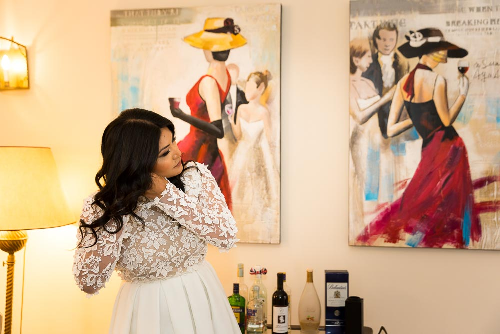 Indoor bridal preparation next to fashion paintings