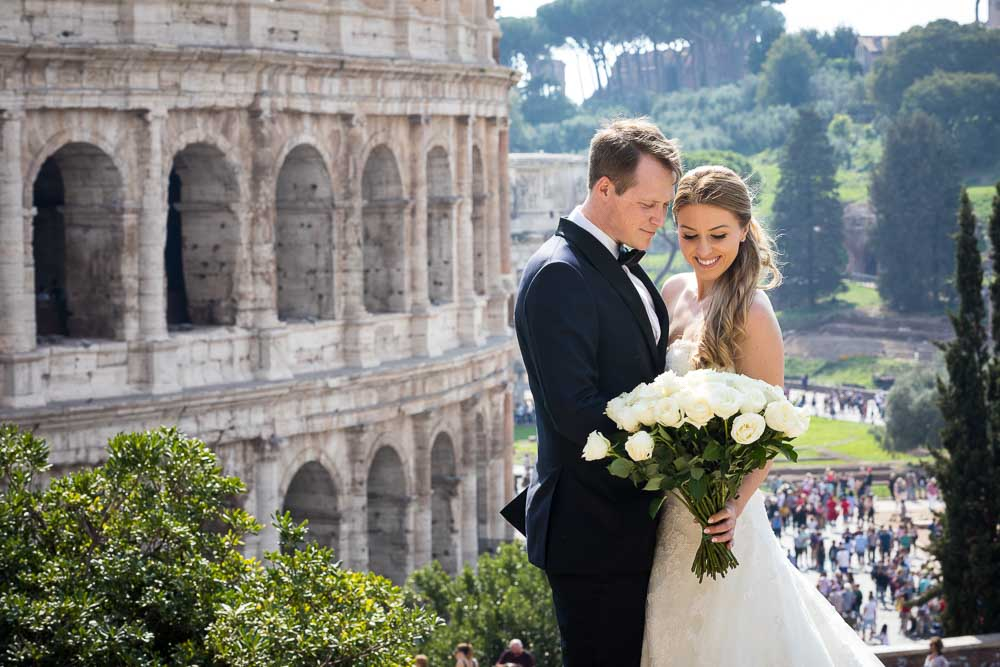 Bride and groom portrait posing by the Roman Colosseum in the far distance. Image by Andrea Matone photographer
