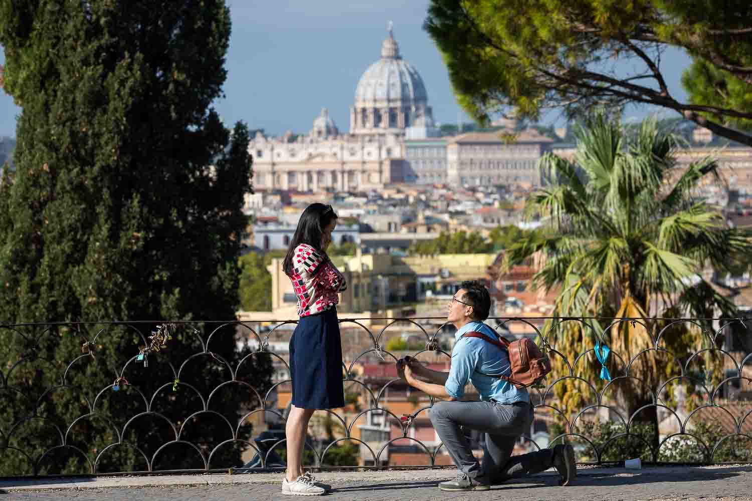 Man knee down proposing marriage before the scenic view of the Roman skyline and Saint peter's dome in the far distance