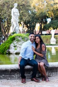 Portrait picture of a newly engaged couple sitting on the edge of a water fountain