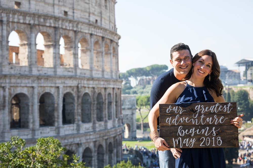 Portrait picture by the Colosseum holding a a sign