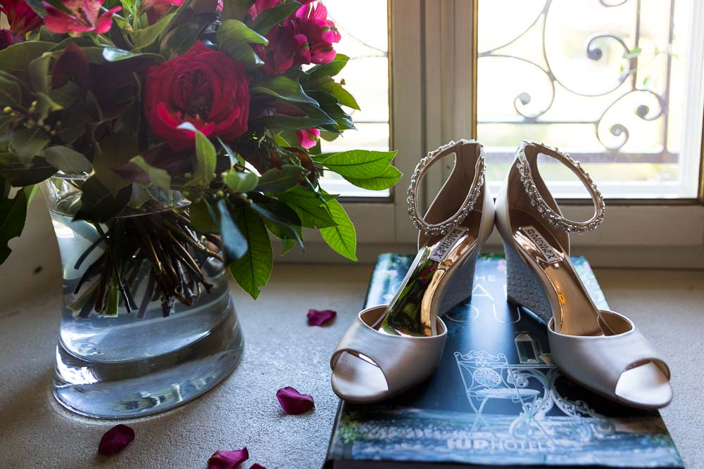 Bridal shoes photographed in window light next to red flowers