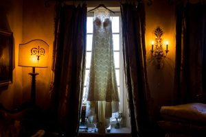 The bridal dress hanging from the window