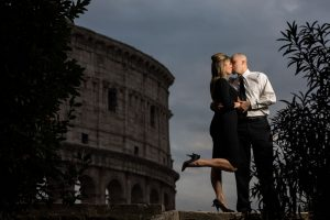 Kissing by the Roman Colosseum at dusk. Portrait photo session in Rome Italy