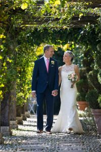 Bride and groom walking together in the villa park