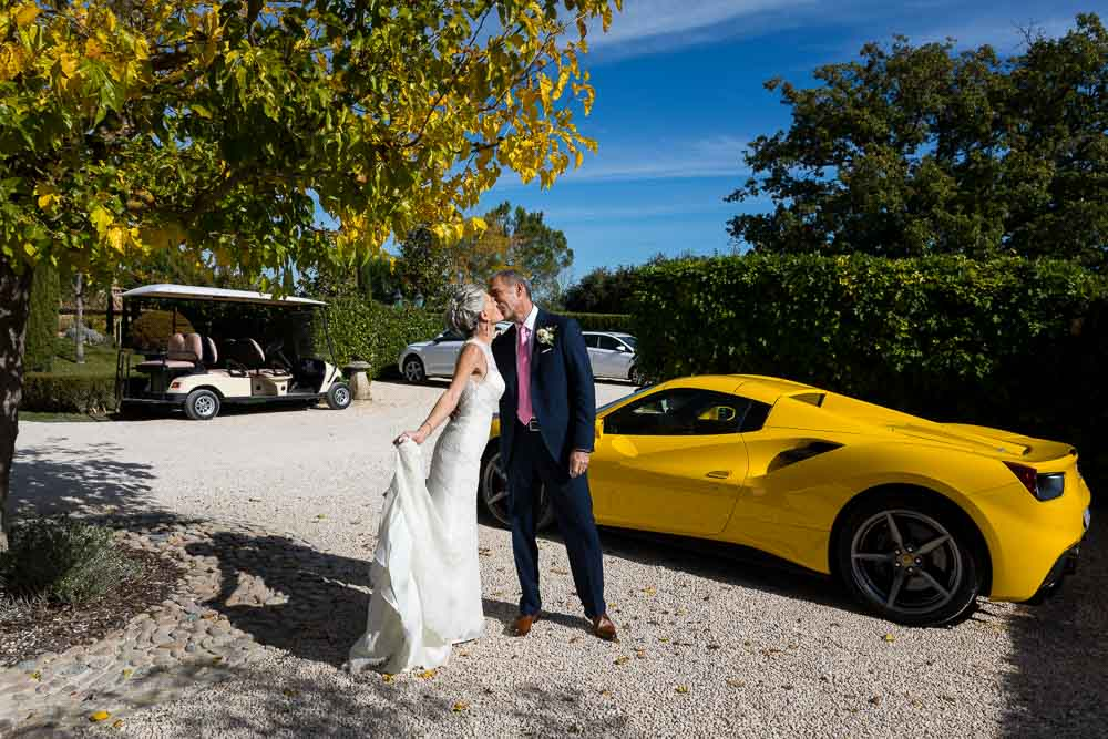 Newlyweds with a bright yellow Ferrari sports car