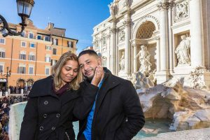 Couple posed close to one another at Fontana di Trevi