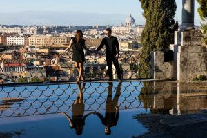 Couple holding hands with water reflection at Parco del Pincio