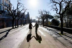 Couple walking away holding hands in silhouette