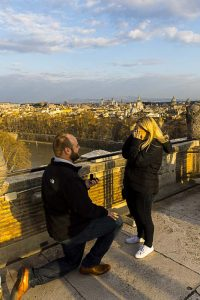 Man proposing marriage on top of the Castel Sant'Angelo terrace in Rome Italy