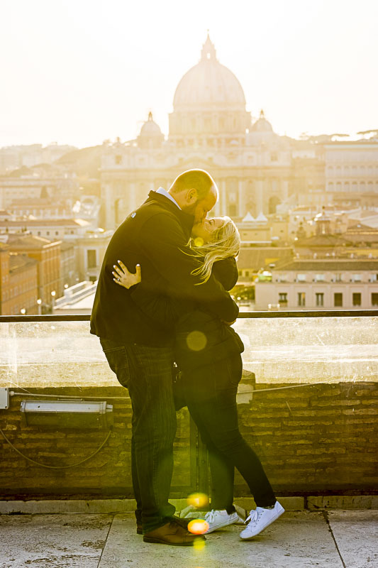 Kissing at sunset in front of Saint Peter's dome in the far distance