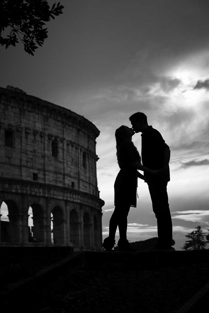 Italy Photoshoot. Just engaged kissing in front of the Coliseum in Rome Italy. Black and white fine art image by the Andrea Matone photography studio