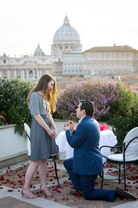 Man proposing marriage on top of a rooftop terrace overlooking the city of Rome from above at sunset