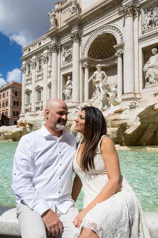 Coupe sitting down posing on the water edge of the Trevi fountain