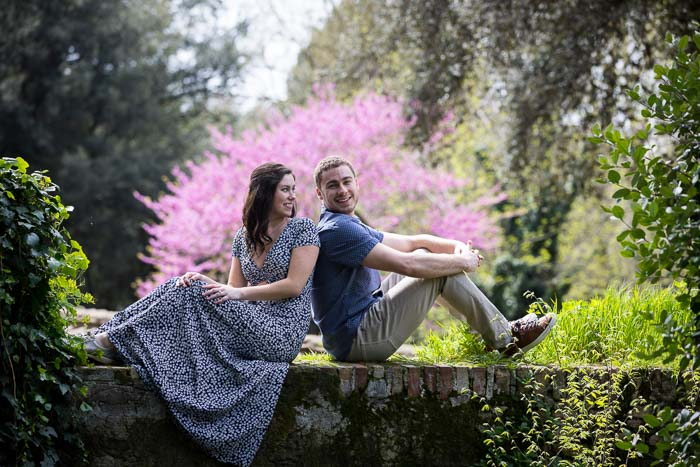 Final couple portrait sitting down on a ledge with a colorful tree in the background
