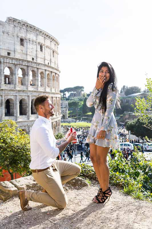 Man proposing in front of the roman Coliseum in Rome Italy