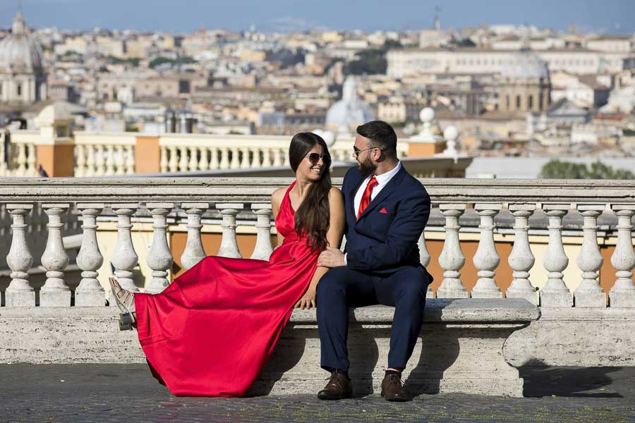 Photo shoot of a couple sitting down on a marble bench overlooking the roman skyline in the background