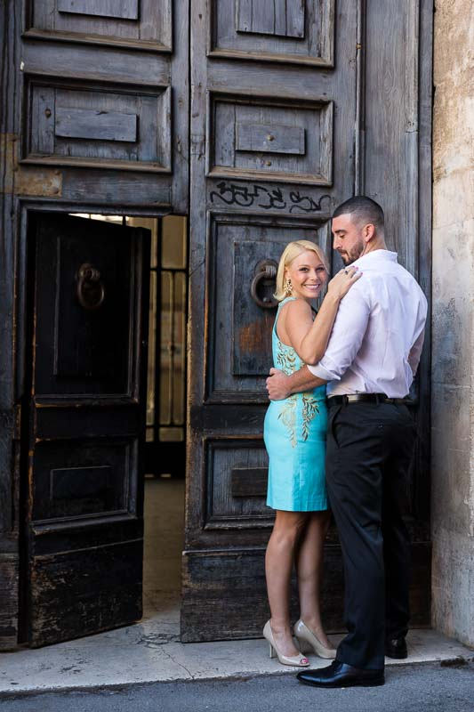 Couple posing in front of an old doorway in the roman streets