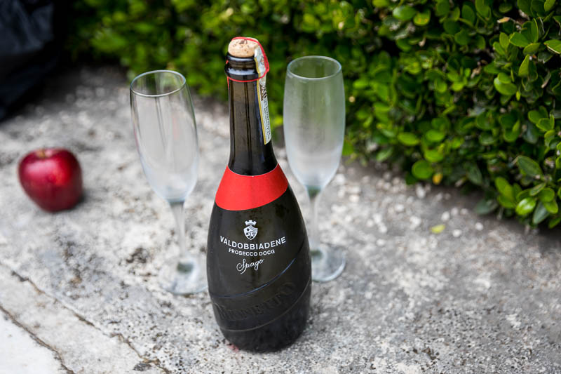 Italian Prosecco wine bottle close up with glass flutes and an apple
