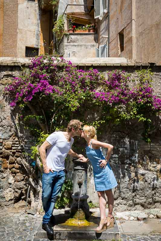 Kissing by a drinking water fountain in the streets of the old quarter of Trastevere