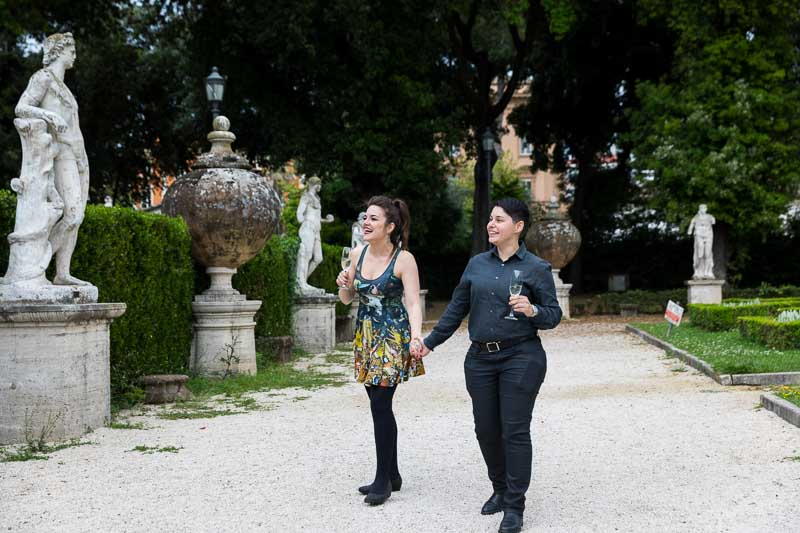 Same sex couple walking together in a roman park with ancient marble statues on the sides