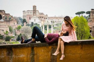 Relaxed together before the ancient city and the Coliseum in the far distance