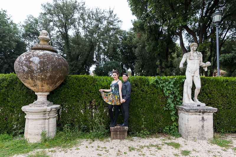 Portrait picture of a gay couple posing next to roman statues