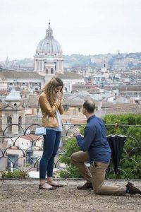 Man knee down proposal at the belvedere park terrace overlooking the ancient city of Rome