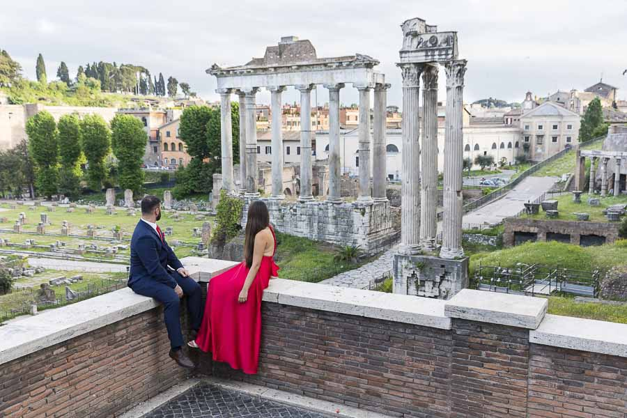 Looking at the ancient roman ruins at the Forum during an engagement photo session