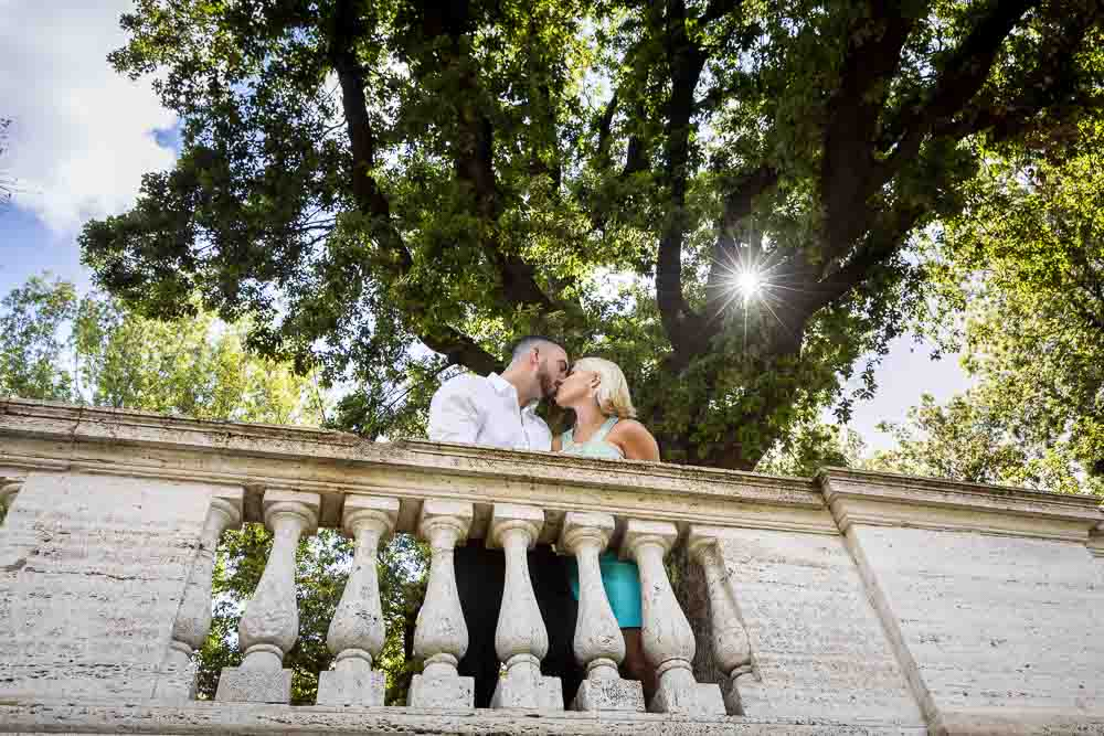 Couple engagement photography session in Italy. Kissing on a balcony.