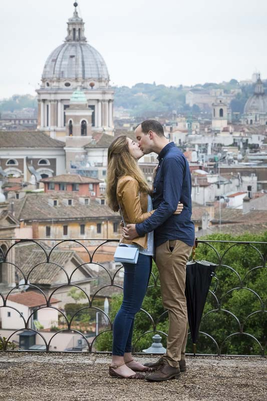 Kissing in love before the panoramic view of the roman rooftops