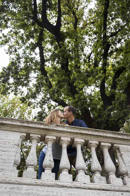 Kissing underneath tree on a terrace overlook