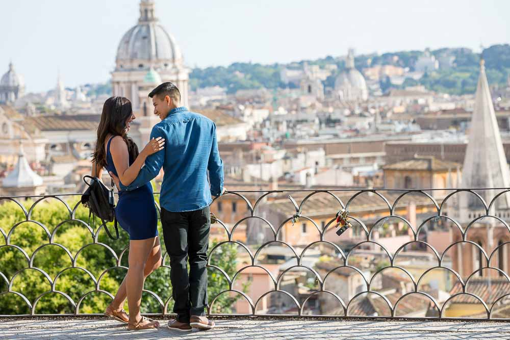 Couple overlooking the roman skyline from the picnian hill just before a wedding marriage proposal in Rome Italy