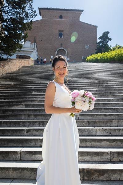 Radiant bride portrait standing on the steps of Church Basilica di Santa Maria in Ara coeli in Rome