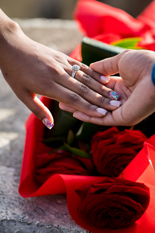 Close up image of the engagement ring over red roses