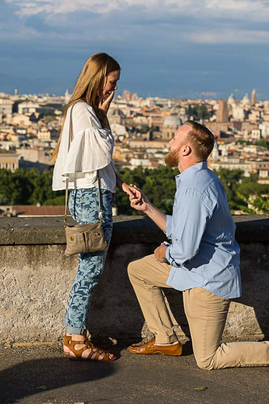 Man proposing marriage to fiance before the sweeping view of the roman skyline