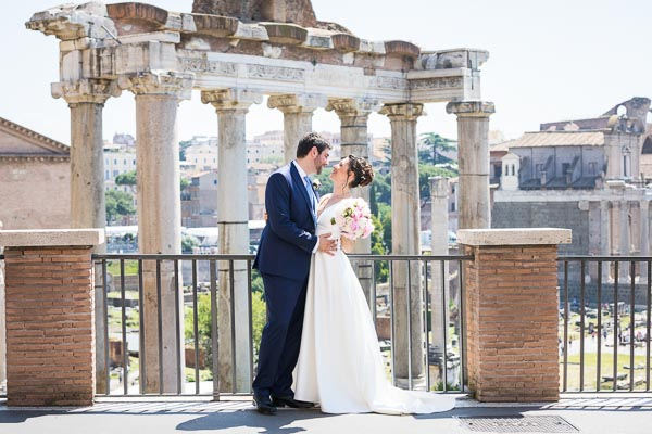 Bride and groom taking pictures before the roman forum in Rome Italy