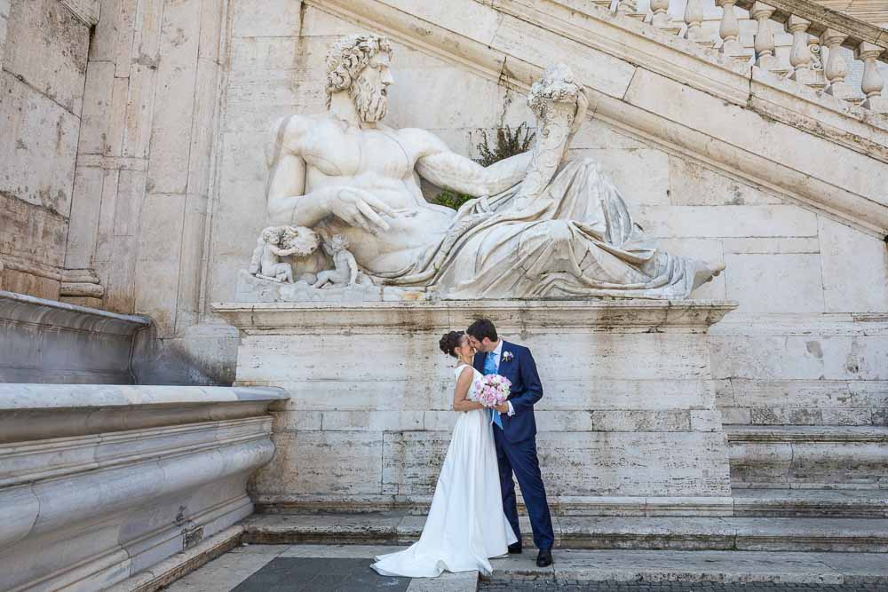 Wedding day photography of a couple standing underneath an ancient marble roman statue