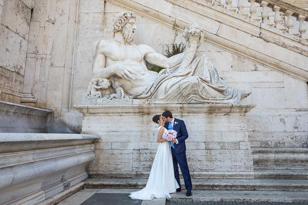 Couple just married kissing under and ancient roman marble statue