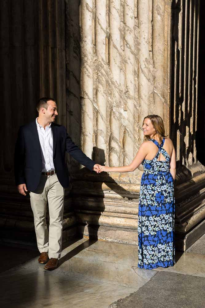 Just engaged walking hand in hand in between ancient columns