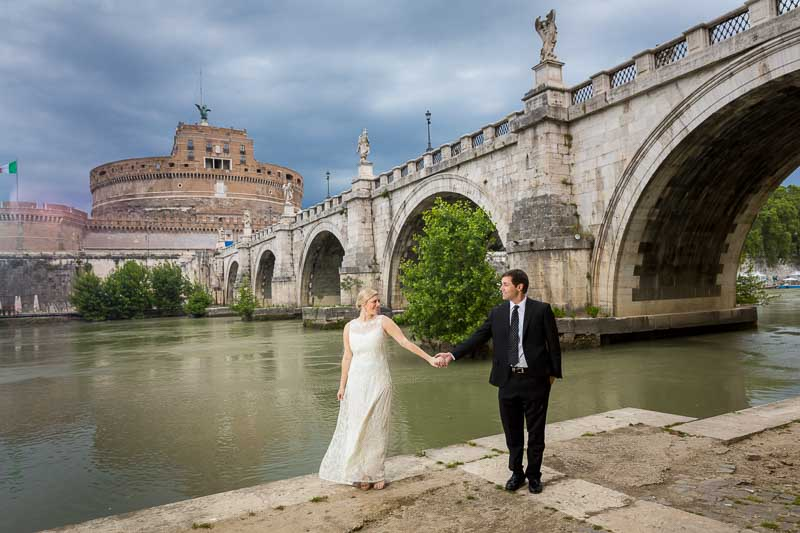 Holding hands down below the Tiber river with the Castle in the far distance