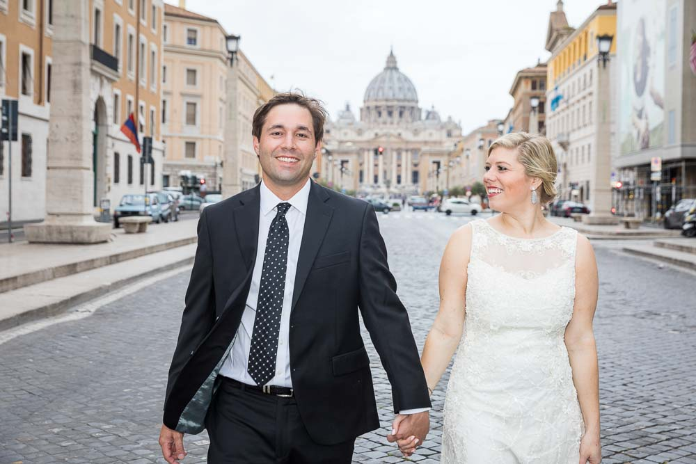 Bride and groom holdings hands and walking together in Via della Conciliazione with Saint Peter's in the background