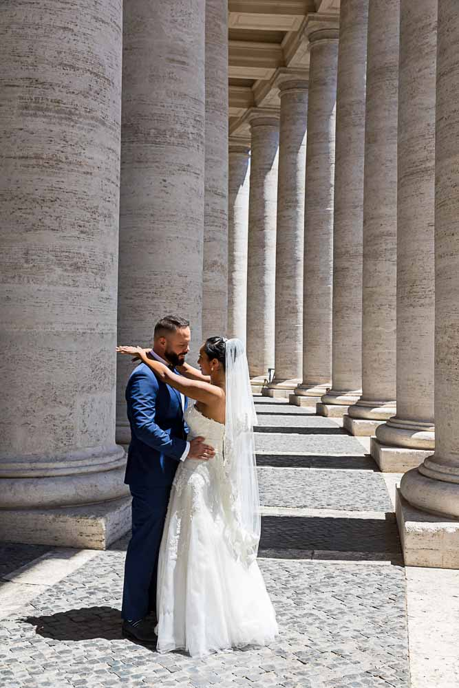 Bride and groom posed photo under the Saint Peter's colonnade in the Vatican