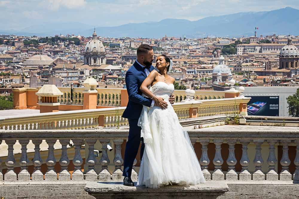 Newlyweds standing before the roman skyline from the Janiculum hill in Rome