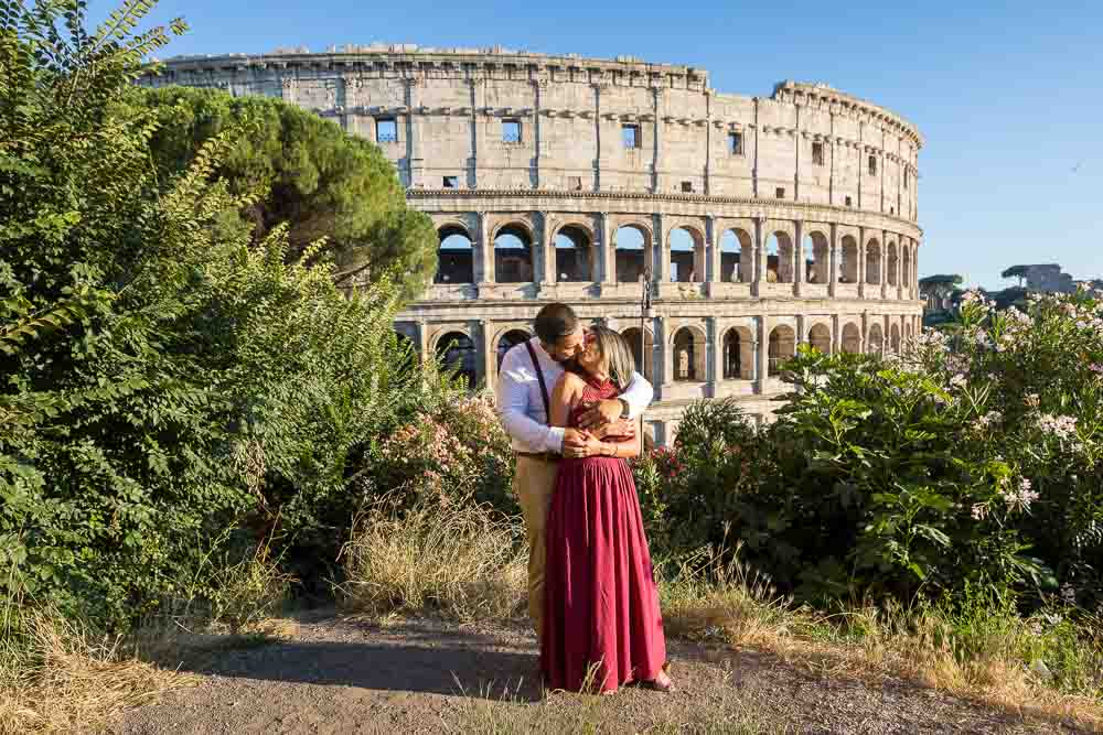 Posing for a portrait picture at the Roman Colosseum. Couple standing together and kissing before one of the main iconic landmarks in Rome